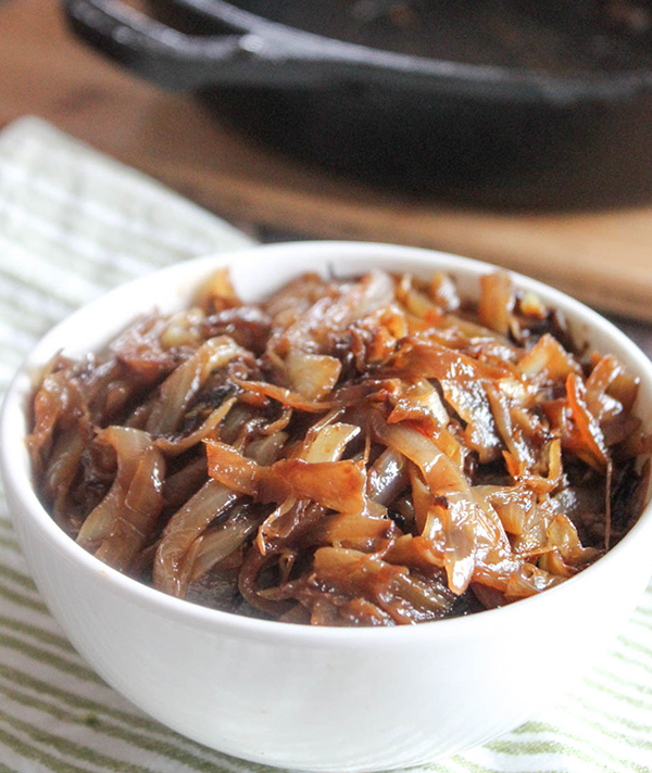 A white bowl filled with caramelized onions