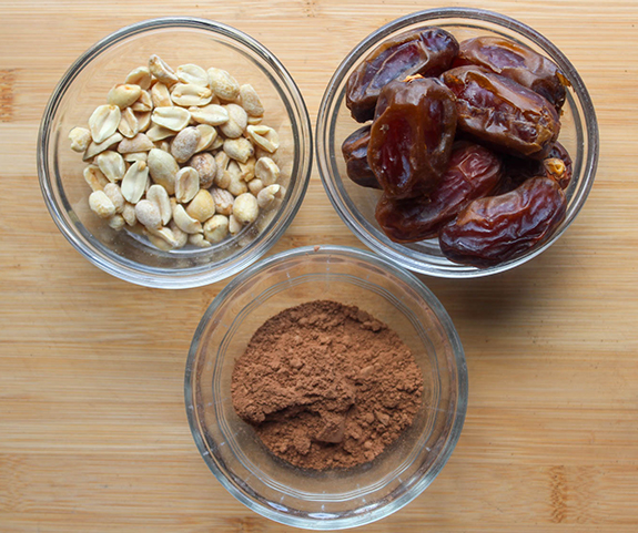 Peanuts, dates and coco powder in glass bowls