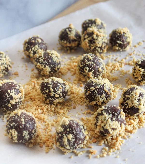 Energy bites rolled in chopped peanuts on parchment paper
