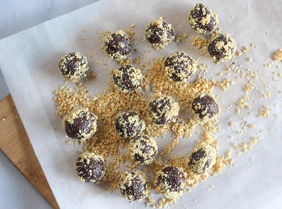 overhead view of the completed chcoloate energy bites with chopped peanuts on parchment paper