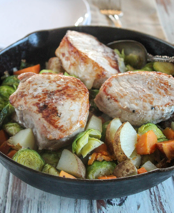 easy oven baked pork chops with vegetables in a skillet