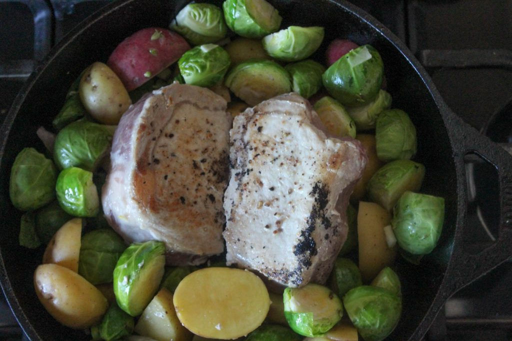 pork chops in a skillet with vegetables