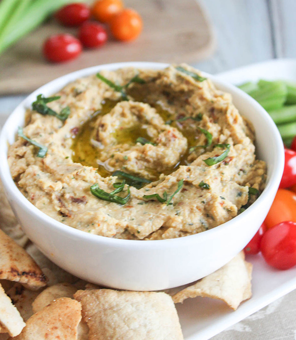 a bowl of hummus with pita chips and tomatoes