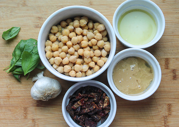 Ingredients: chickpeas, lemon juice, olive oil, sun dried tomatoes, garlic and basil in white bowls