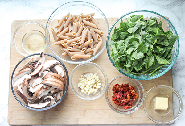 The ingredients on a board: pasta, spinach, mushrooms, garlic, sun dried tomatoes, butter, white wine