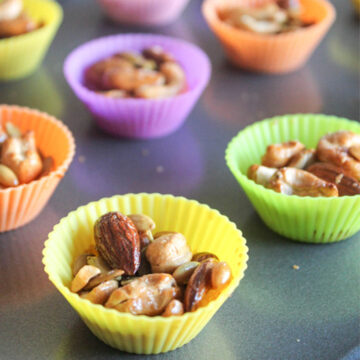 cashew clusters in colorful silacone cupcake holders on a baking sheet