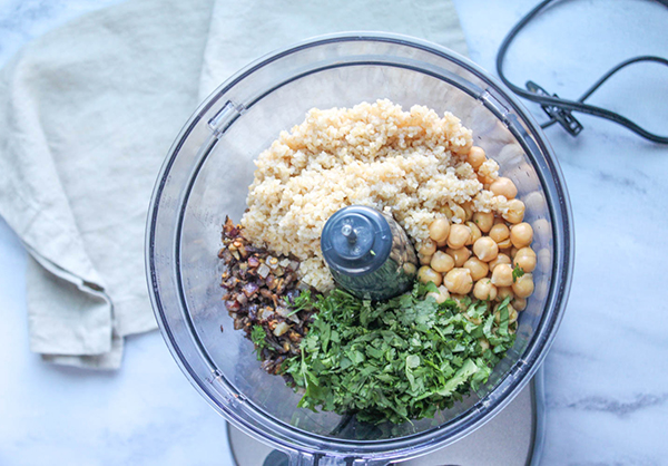 fresh herbs, chickpeas, bulger wheat and onions in a food processor bowl