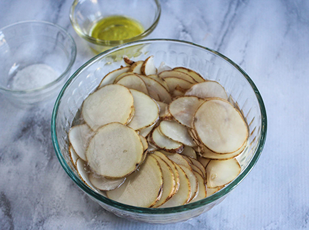 Potato slices in a bowl with oil
