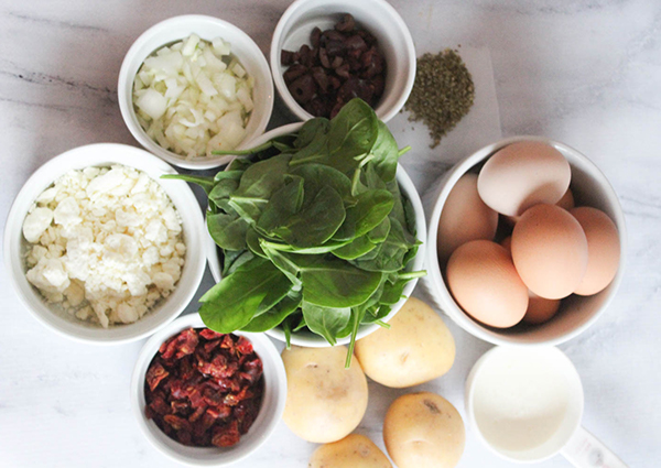 The ingredients in bowls: spinach, potatoes, milk, eggs, cheese, onons, olives and oregano