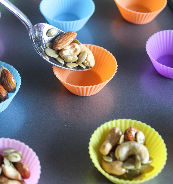 a spoon placing the nut mixture into a cupcake liner