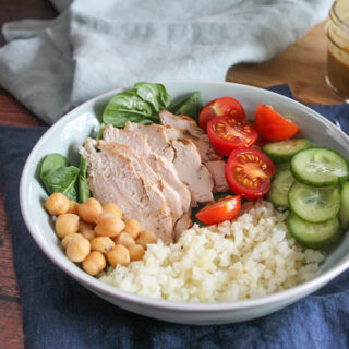 cauliflower rice, cucumbers, tomaotes, spinach, chicken and chickpeas in a bowl