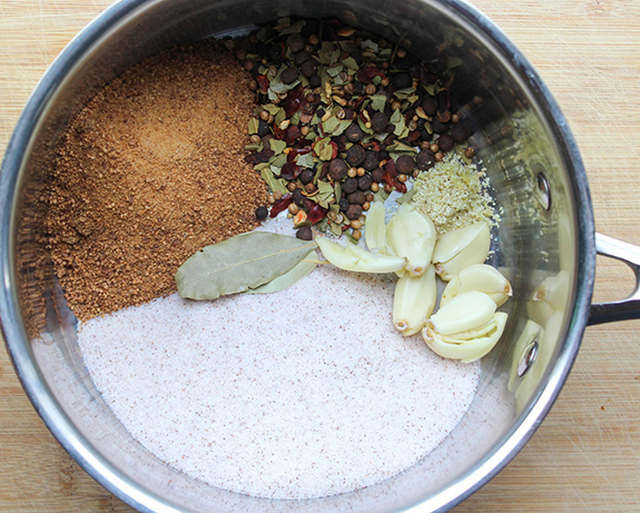 Ingredients in a pot: sea salt, garlic cloves, bay leaves, pickling spice and coconut sugar