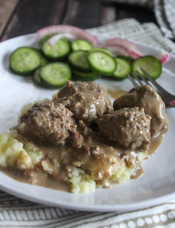 swedish meatballs on a plate with mashed potatoes and cucumbers