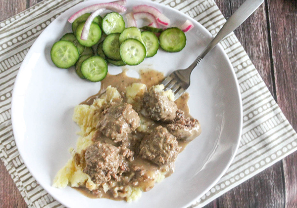 overhead view of meatballs on a plate with cucumbers
