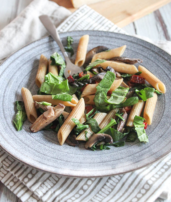 a close up of spinach and mushroom pasta on a plate