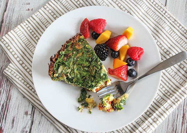 overhead view of quiche on a plate with fresh fruit