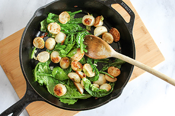 Sauteed greens with roasted turnips in a pan