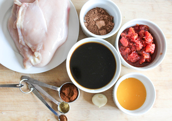 THe ingredients on a board: chili powder, cumin, garlic, orange juice, tomatoes, coffee, cocoa powder and boneless chicken breasts
