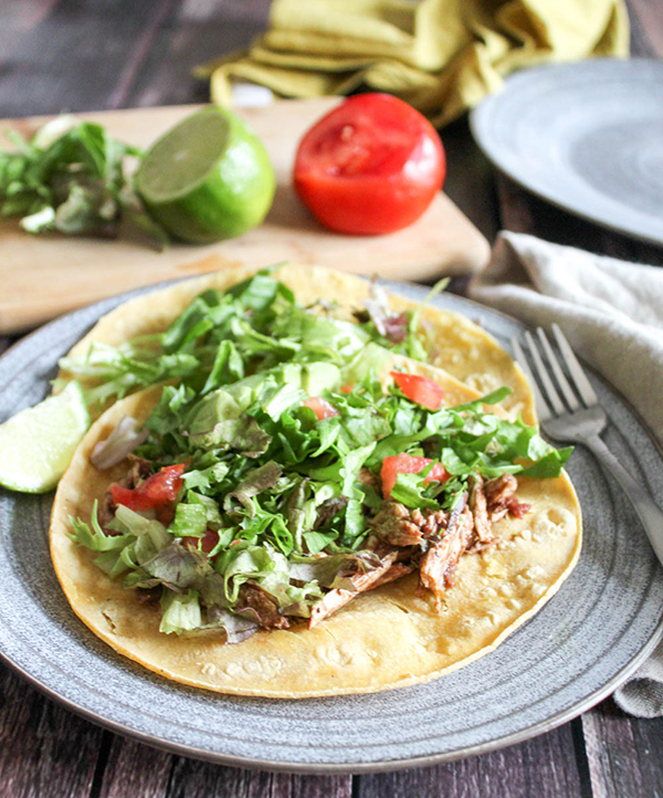 shredded chicken with lettuce on top of a tortilla