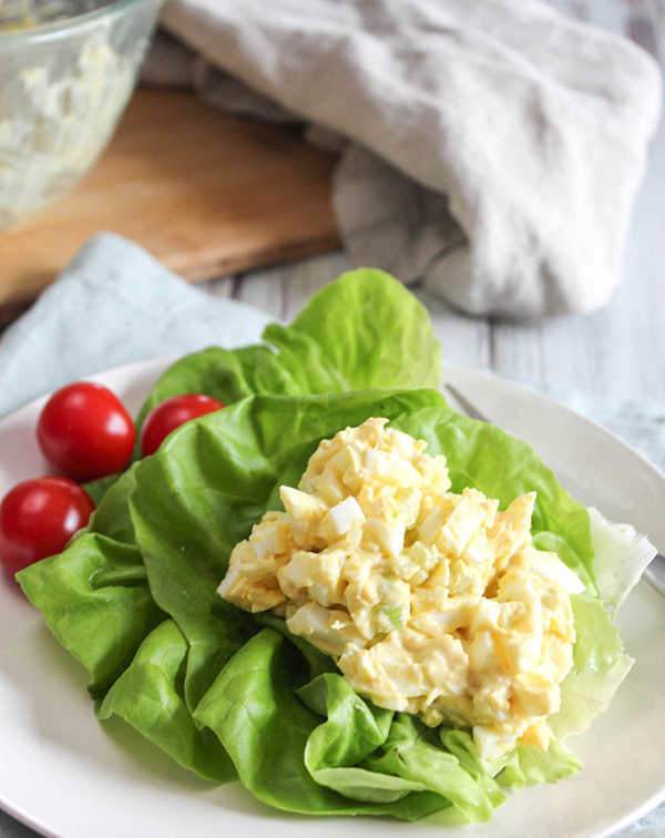A big scoop of egg salad on lettuce with tomatoes on a white plate