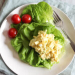 an overhead view of egg salad on a bed of lettuce on a white plate with tomaotes