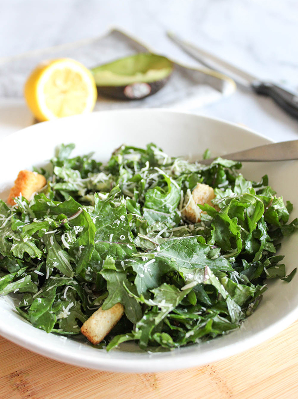 kale caesar salad in a bowl with a fork