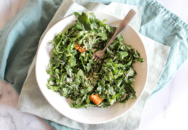 An overhead view of kale caesar salad with a fork