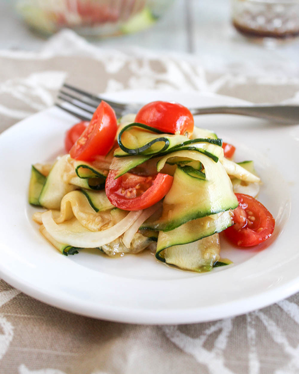 zucchini ribbon salad on a white plate with a fork