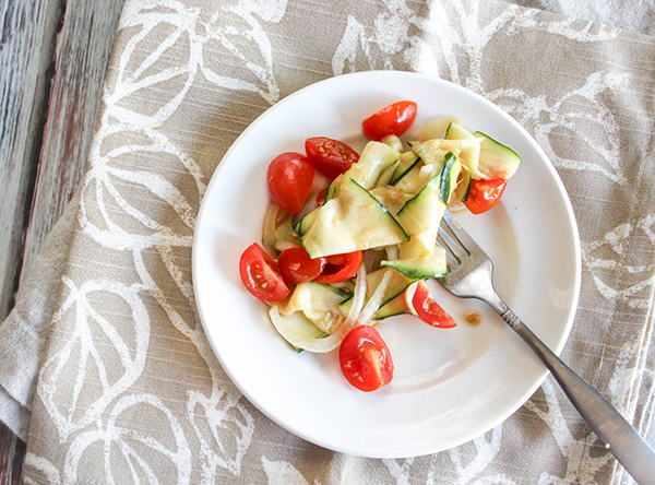 an overhead veiw of zucchini tomatoes and onions in a salad on a plate
