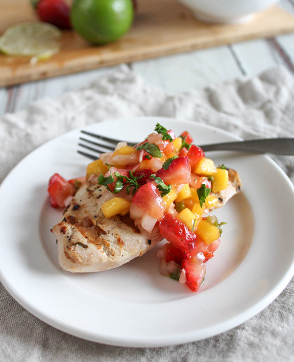 mango salsa on top of grilled chicken on a white plate