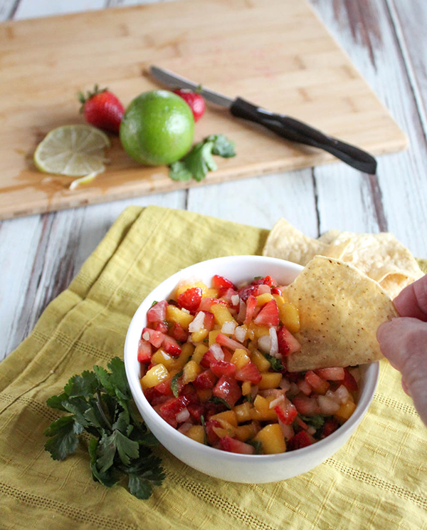 A bowl of salsa with a chip being dipped into it.