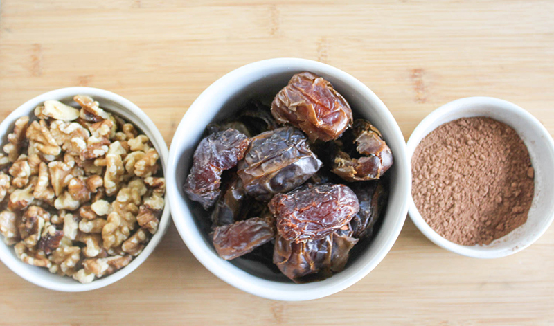 The ingredients in separate bowls: walnuts, dates, cocoa powder