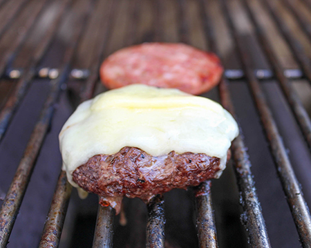 burger with melted cheese on the grill