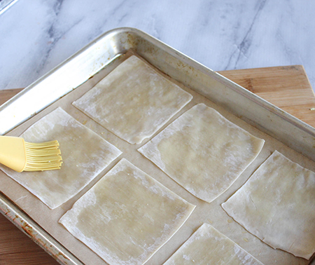 wonton wrappers on a baking sheet with a brush covering them with oil