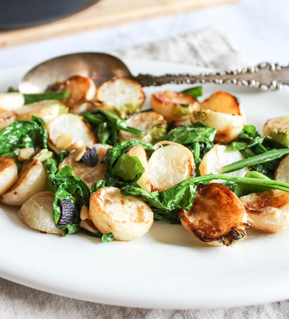 turnips and greens on a white plate with a serving spoon