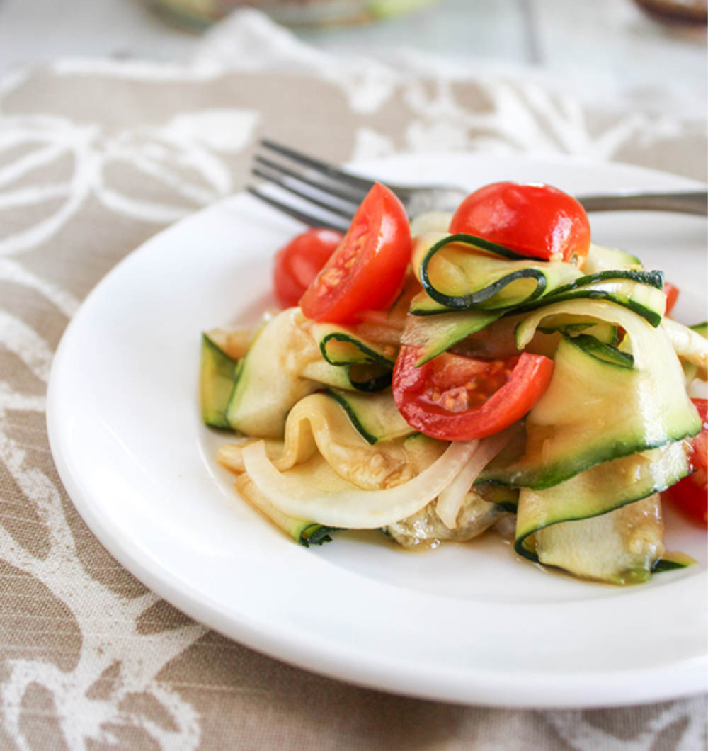 zucchini ribbons with cherry tomatoes on a white plate with a fork