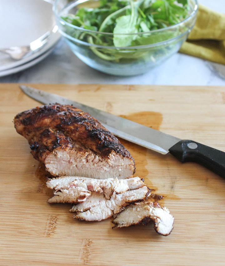 grilled chicken breast on a cutting board sliced with a knife