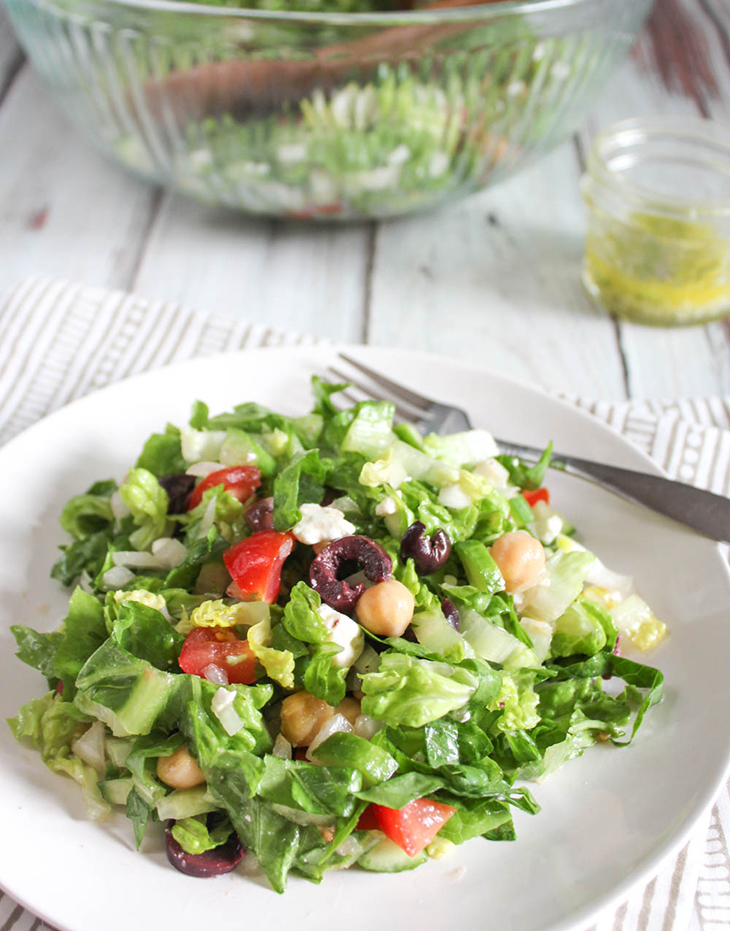 greek chopped salad on a white plate with a fork