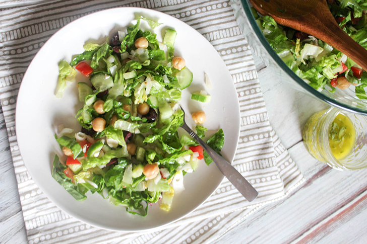 On overhead view of salad on a white plate with a fork