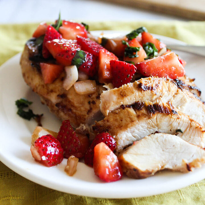 sliced chicken on a plate with strawberry salsa