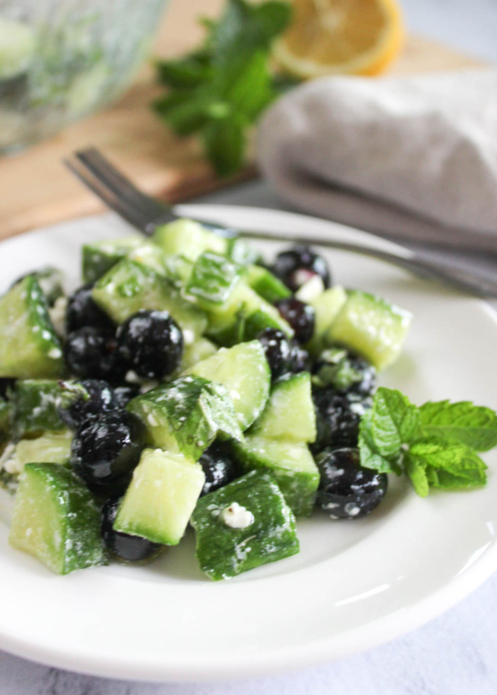 close up photo of summer cucumber salad: diced cucumbers with blueberries and feta cheese on a white plate with a sprig of mint