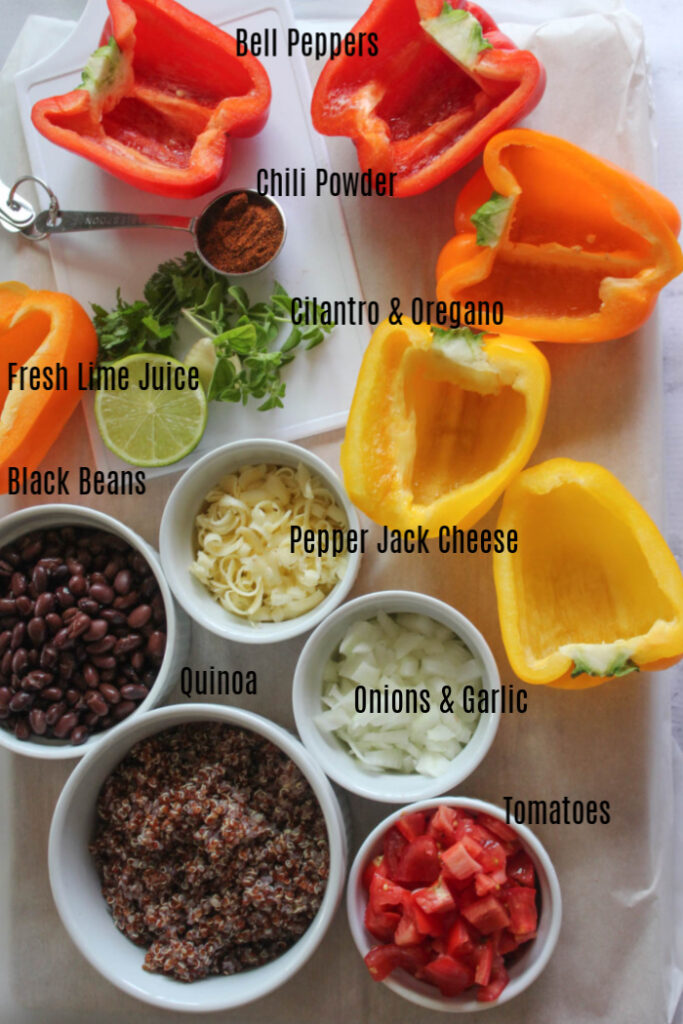 The ingredients on a board, bell peppers, chili powder, cilantro and oregano, lime, shredded cheese, black beans, onions, cooked quinoa and tomatoes