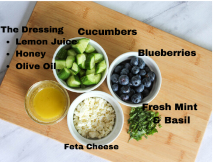 The ingredients for the salad: cucucmbers, blueberries, mint, basil, cheese and lemon dressing