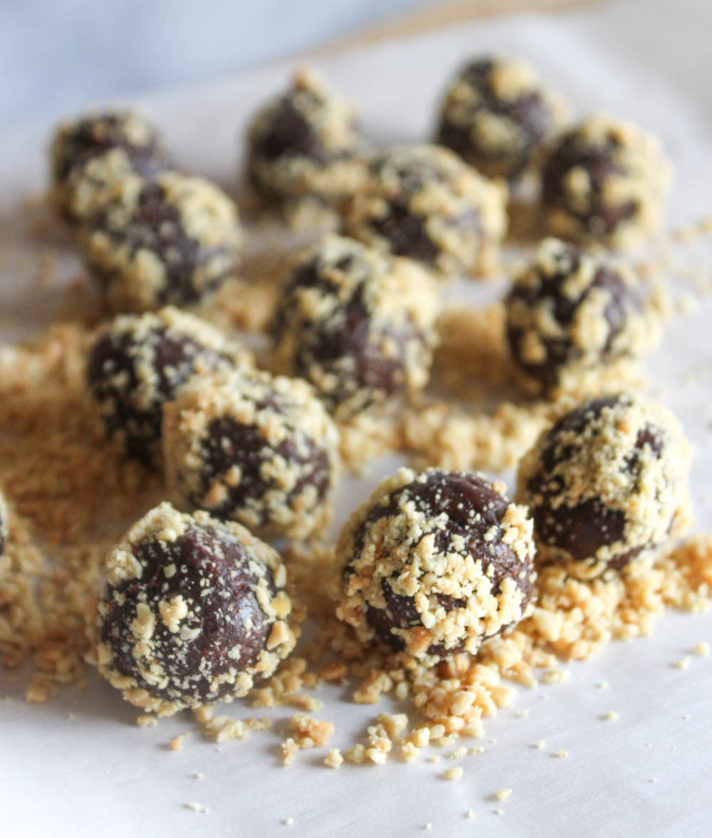 chocolate balls on parchment paper with peanuts crumbles