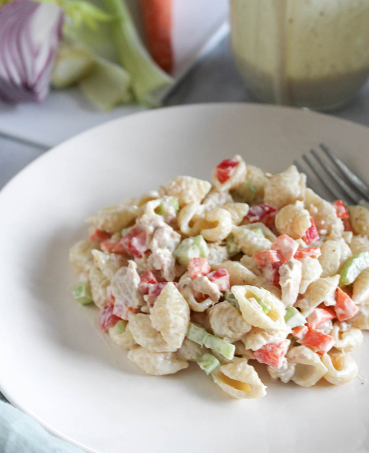a close up view of the pasta salad on a white plate with a fork