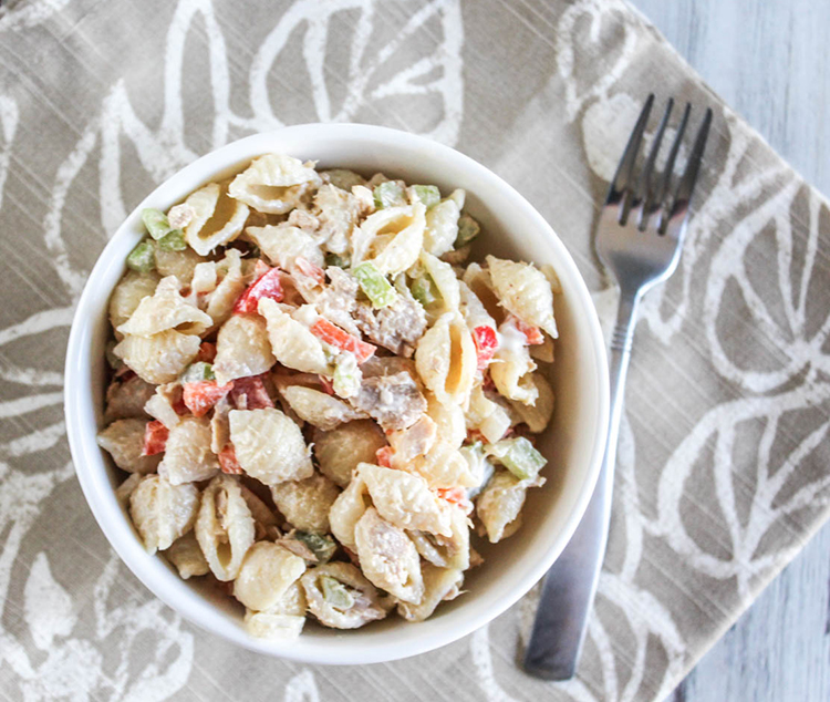 A view looking down at tuna mac salad in a white bowl with a fork