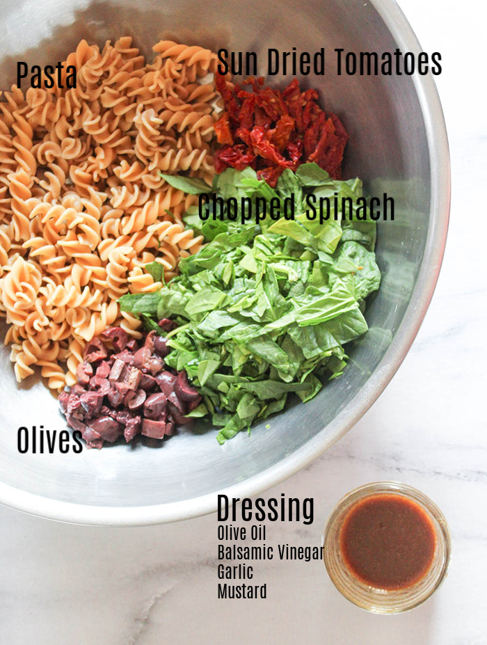 spinach pasta salad ingredients in a mixing bowl