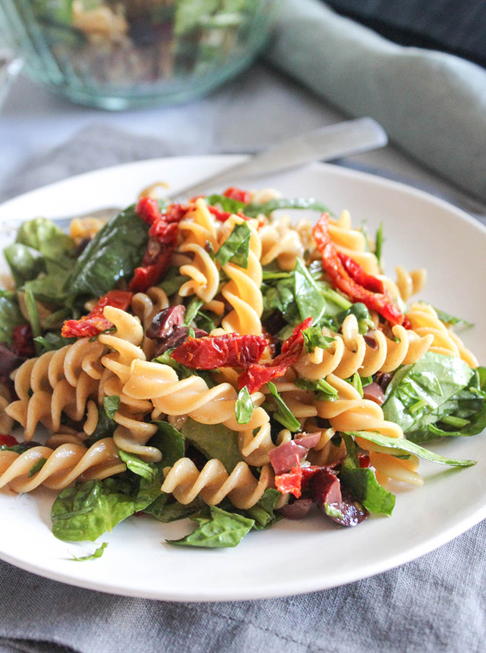 spinach pasta salad on a white plate