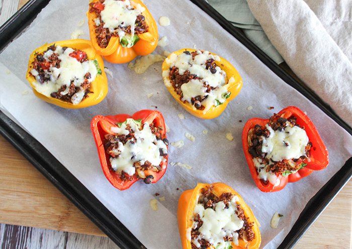 An overhead view of stuffed peppers on a baking pan with melted cheese