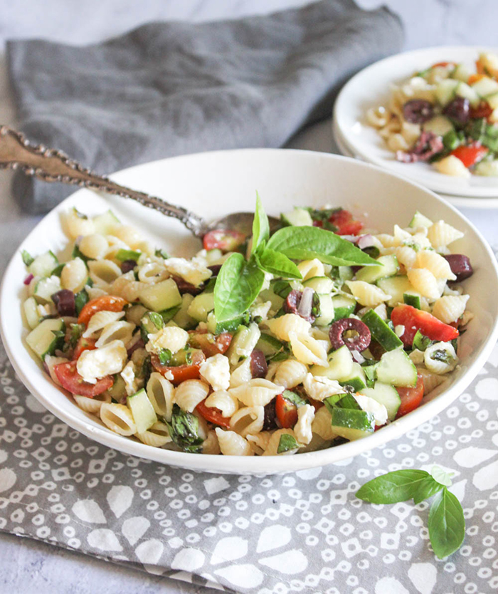 Greek Pasta Salad in a bowl  with a spoon and fresh basil on top